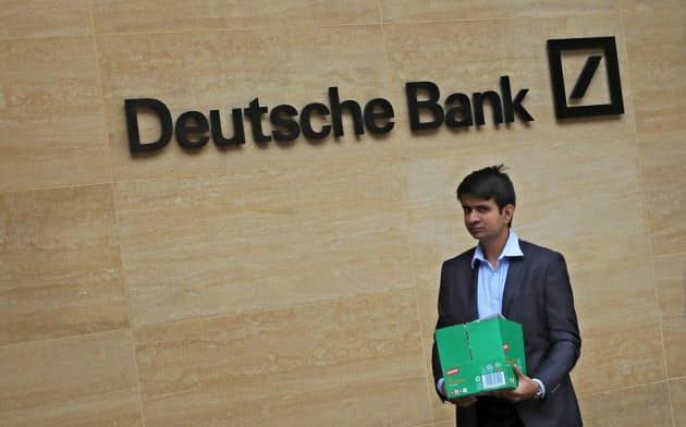 私物を入れた箱を抱え、銀行を去る従業員。ドイツ銀は7日、全行員の2割にあたる1万8千人の削減を柱とする再建計画を発表した=ロイター