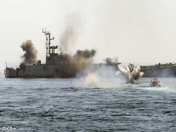 ホルムズ海峡で船舶を襲撃する訓練をするイラン革命防衛隊の小型ボート(手前右)=ロイター