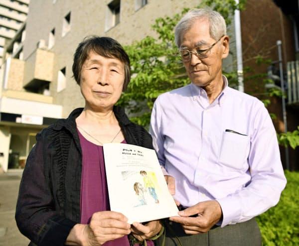 講演後、銃根絶の願いを込め自費出版した絵本を手にする服部剛丈さんの母、美恵子さん(左)と父の政一さん(6月22日午後、名古屋市の名古屋市立大)=共同