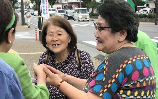 有権者と握手する参院選立候補者(左)(10日、滋賀県彦根市)