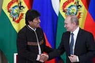11日、ロシアのプーチン大統領(右)と握手するボリビアのモラレス大統領(モスクワ)=ロイター