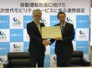 協定締結後に握手する加賀市の宮元市長(右)とモネ・テクノロジーズの柴尾副社長(12日、石川県加賀市)