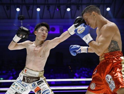 3回、ジョナサン・タコニン(右)にパンチを浴びせる拳四朗(12日、エディオンアリーナ大阪)=共同