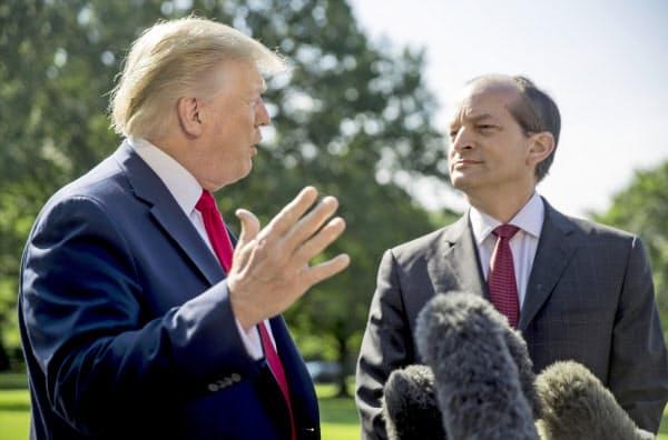 トランプ大統領とともに記者団に対応するアコスタ労働長官(右)=AP
