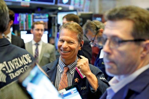 連日の最高値更新で笑顔を見せるトレーダーら(12日、ニューヨーク証券取引所)=ロイター