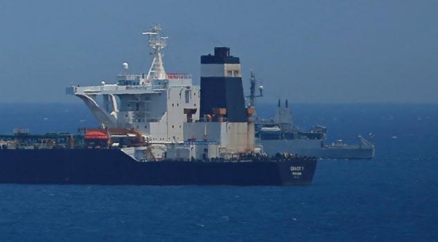 イラン産とみられる原油をシリアに輸送しようとして拿捕された大型タンカーと英海軍艦船=ロイター