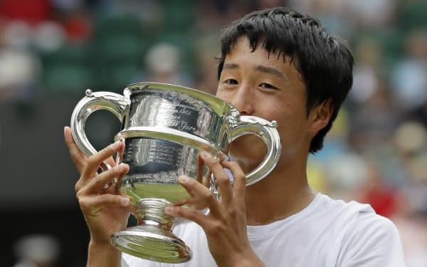 ウィンブルドン・ジュニア選手権の男子シングルスで優勝し、カップを手に喜ぶ望月慎太郎(14日、ウィンブルドン)=AP