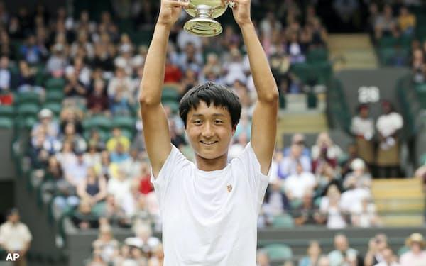 テニスのウィンブルドン・ジュニア選手権の男子シングルスで日本勢初優勝を果たし、カップを掲げて喜ぶ望月慎太郎選手(14日、ウィンブルドン)=AP
