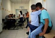 米国への難民申請の順番を待つエルサルバドル人の親子=ロイター