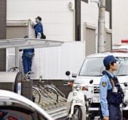 住人の男子高校生が男に襲われた住宅の周囲を調べる捜査員(16日午前、埼玉県蕨市)=共同