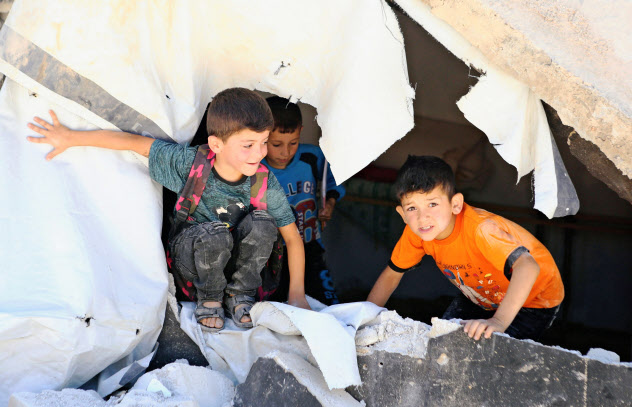 Syrian refugee kids play on rubble of dismantled concrete huts at a makeshift Syrian refugee camp in the Lebanese border town of Arsal, Lebanon July 4, 2019. Picture taken July 4, 2019. REUTERS/Mohamed Azakir