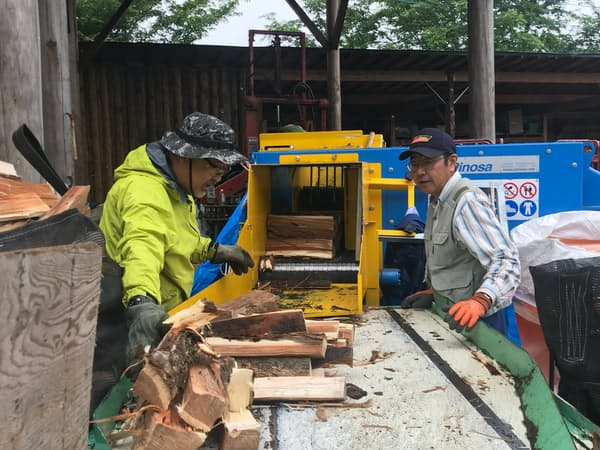 きたもっく(群馬県長野原町)では自動薪割り機に玉切りしたナラの丸太を入れて薪にカットする