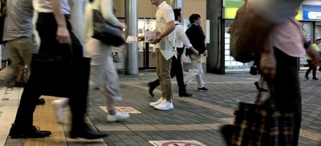 1人で駅前に立ちビラを配る立候補予定の男性(6月下旬)