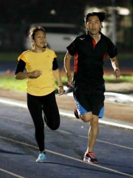 照明がともる中、高田千明(左)の伴走で100メートルを走る大森