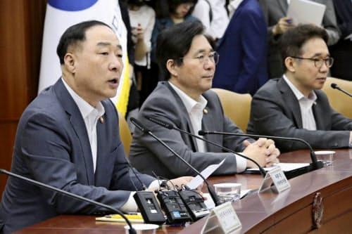 韓国の洪楠基・経済副首相兼企画財政相(左)(8日、ソウル)=聯合・共同
