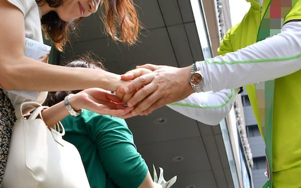 有権者と握手する参院選の立候補者(右)(大阪市中央区)
