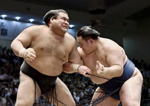 14日の大相撲名古屋場所8日目、玉鷲(右)に左肘付近を攻められ、顔をゆがめる高安(ドルフィンズアリーナ)=共同