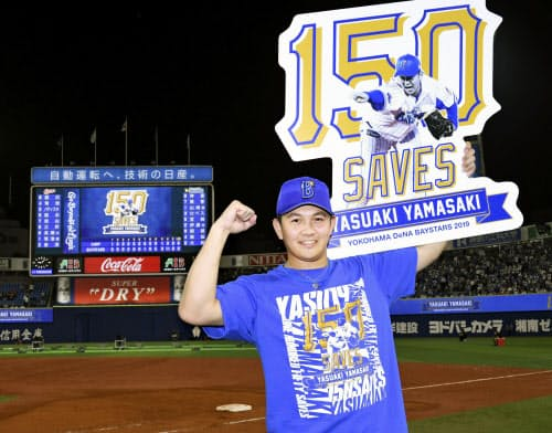 史上最年少での通算150セーブを達成し、記念のボードを手にするDeNA・山崎(17日、横浜)=共同