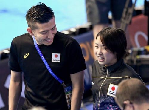 女子高飛び込み決勝の演技を終え、寺内健(左)と話す荒井祭里(17日、光州)=共同
