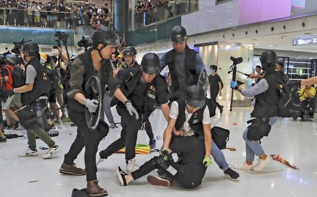 14日、香港・沙田のショッピングモール内で、デモ参加者を取り押さえる警察官=AP