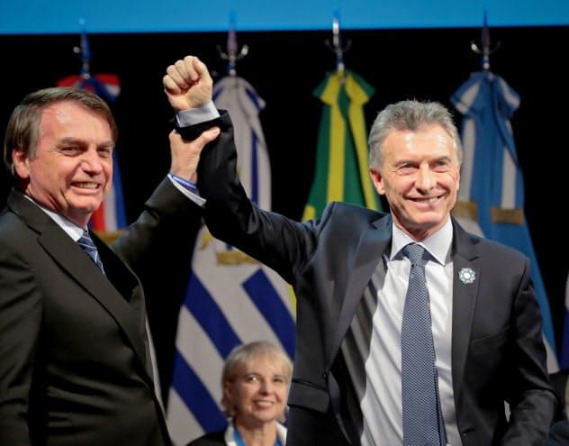 首脳会議に参加したアルゼンチンのマクリ大統領(右)とブラジルのボルソナロ大統領(17日、アルゼンチン北部サンタフェ)=ロイター