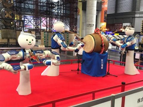双腕ロボット3体が調子を合わせて演奏する(18日、北九州市のJR小倉駅広場)