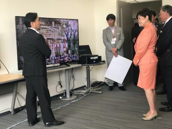 5Gで送信した高精細画像を見る小池知事(18日、東京都練馬区)