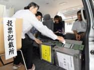 福島県大熊町の住民らが暮らす復興公営住宅前に置かれたワゴン車で期日前投票する町民(17日午後、福島県いわき市)=共同