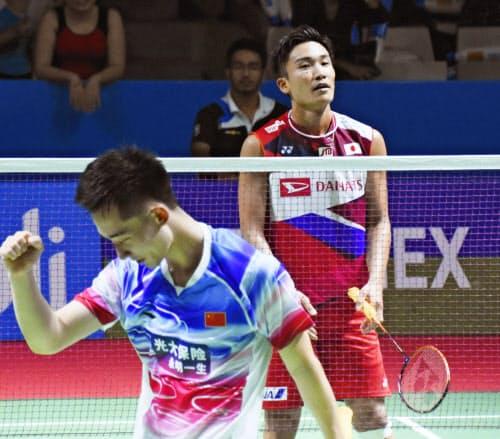 男子シングルス2回戦で、中国選手(手前)に敗れた桃田賢斗(18日、ジャカルタ)=共同