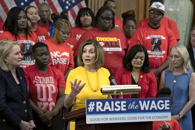 民主党のペロシ下院議長(中)は最低賃金引き上げを主導した=AP