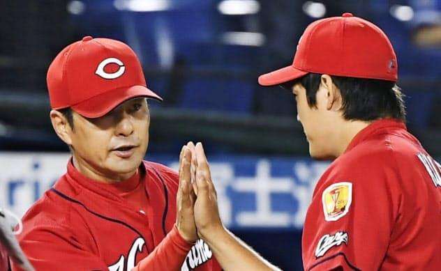連敗を止め、勝利投手の九里(右)とタッチを交わす広島・緒方監督だが、表情はあまり緩まない(15日)=共同