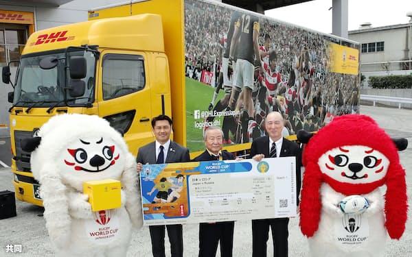 ラグビーW杯のチケット発送が始まり、海外向けの物流センターで記念写真に納まる関係者(18日、東京都内)