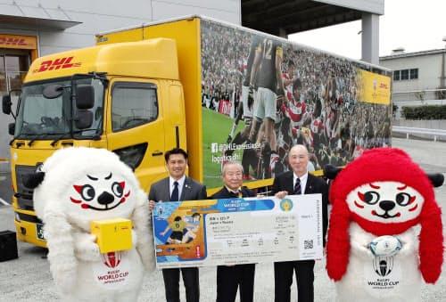 ラグビーW杯のチケット発送が始まり、海外向けの物流センターで記念写真に納まる関係者(18日、東京都内)=共同