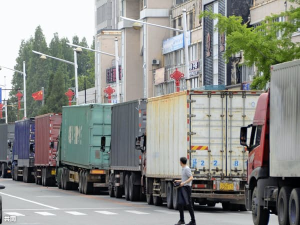 中朝境界で北朝鮮に向かうトラックの列(6月、中国・丹東)=共同