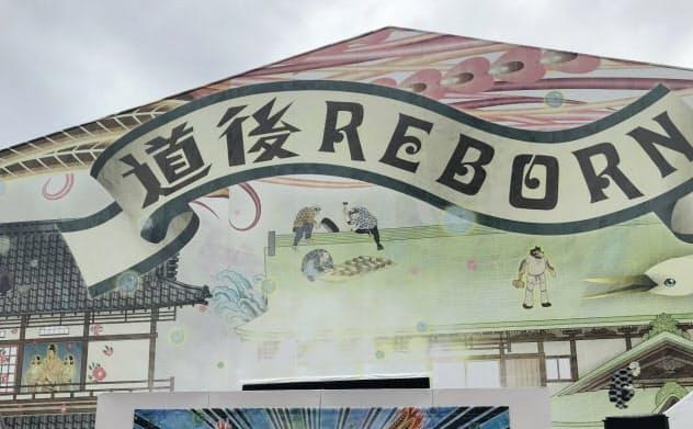 道後温泉本館ラッピングアートを発表する友近さん(中)や松山市の梅岡伸一郎副市長(右)ら(19日)