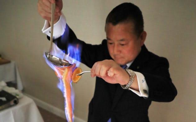 火をつけたブランデーをオレンジの皮にそそぎパイナップルに香りを付ける=淡嶋健人撮影