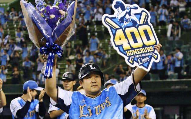 サヨナラとなる通算400本塁打を放ち、記念のボードと花束を手に観客の声援に応える西武・中村=共同