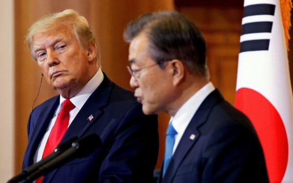 トランプ大統領(左)は日本と韓国で高まっている緊張の緩和に向けた仲介を、文大統領から依頼されたことを明らかにした(写真は6月)=ロイター