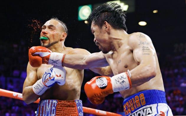 WBAウエルター級王座統一戦でキース・サーマン(左)を攻めるマニー・パッキャオ(20日、ラスベガス)=AP