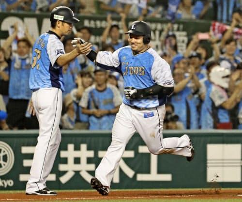 6回、逆転の3ランを放ちコーチとタッチする西武・山川(21日、メットライフドーム)=共同