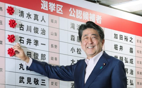 当選のバラをつける安倍首相(21日、自民党本部)