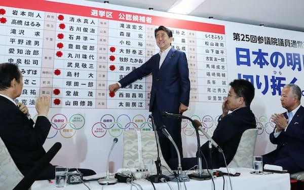 当選のバラを付けて笑顔を見せる安倍首相(21日、自民党本部)