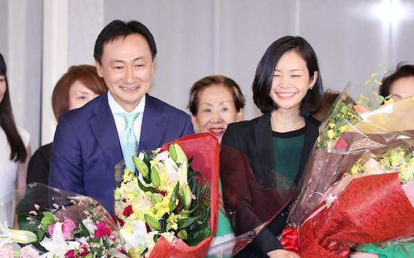 当選が確実になり、花束を手に喜ぶ日本維新の会の東徹氏(左)と梅村みずほ氏(21日午後、大阪市北区)