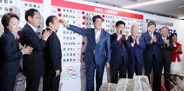 当選のバラをつける安倍首相ら(21日、自民党本部)