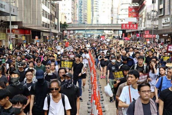 幹線道路を行進するデモ参加者(21日、香港)