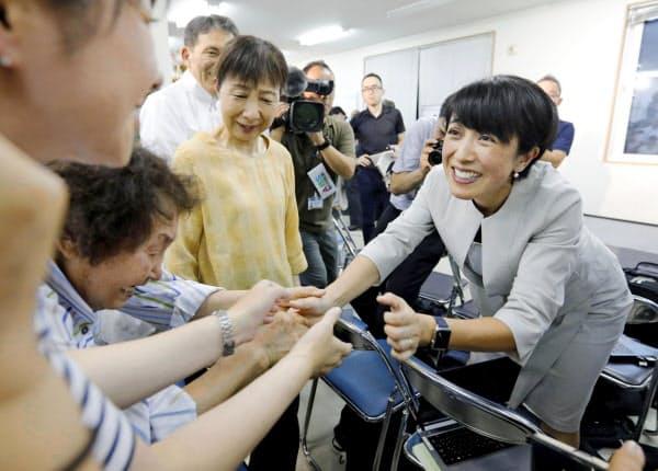 秋田選挙区で当選を決め、支持者と握手する野党統一候補の寺田静氏(右)=21日夜、秋田市、共同