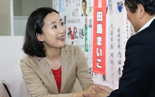 当選を決め、支援者と握手する田島麻衣子氏(左)=21日、名古屋市東区