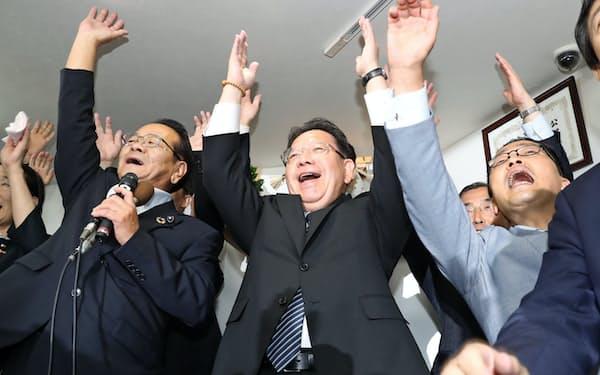 当選を決め、万歳する酒井庸行氏(21日、名古屋市中区)