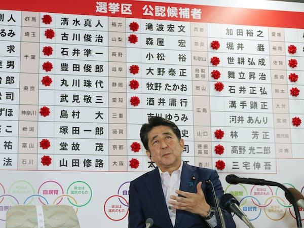 当選確実を示すたくさんのバラを背にインタビューに答える安倍首相(21日、自民党本部)