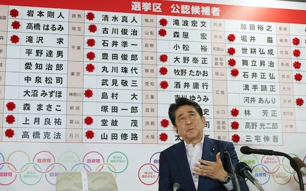 当選確実のバラを背にインタビューに答える安倍首相(21日、自民党本部)